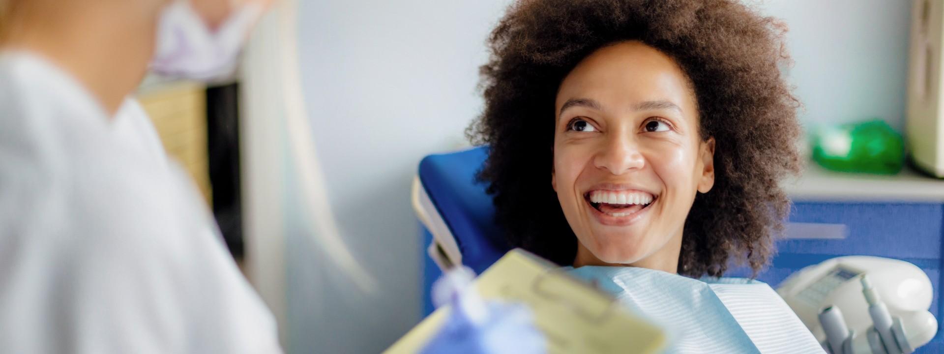 Frau beim Zahnarzt mit strahlendem Lächeln nach der Professionellen Zahnreinigung