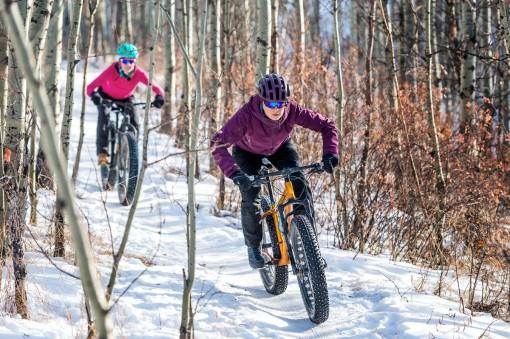 Zwei Jugendliche fahren mit Mountainbikes durch den schneebedeckten Wald.