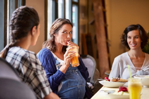 Eine 35-jährige schwangere Frau unterhält sich in einem Café mit ihren beiden Freundinnen.