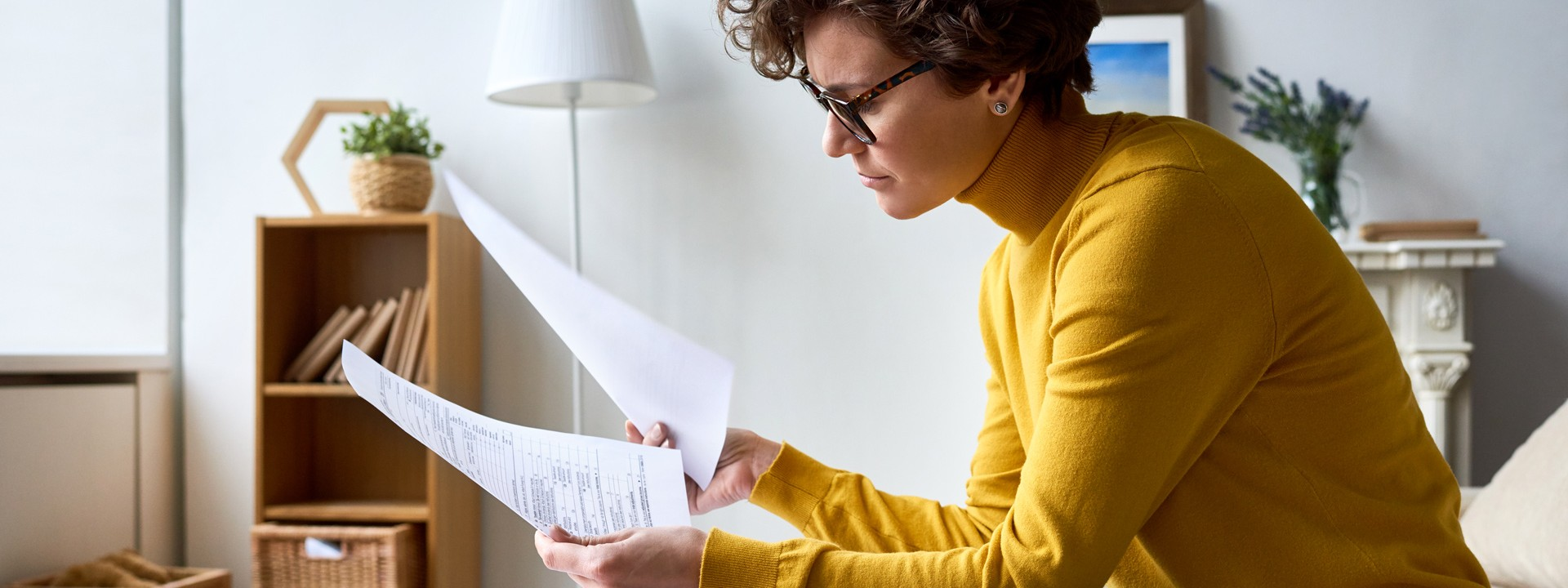Eine Frau im gelben Pullover sitzt auf dem Sofa und schaut sich Unterlagen an.