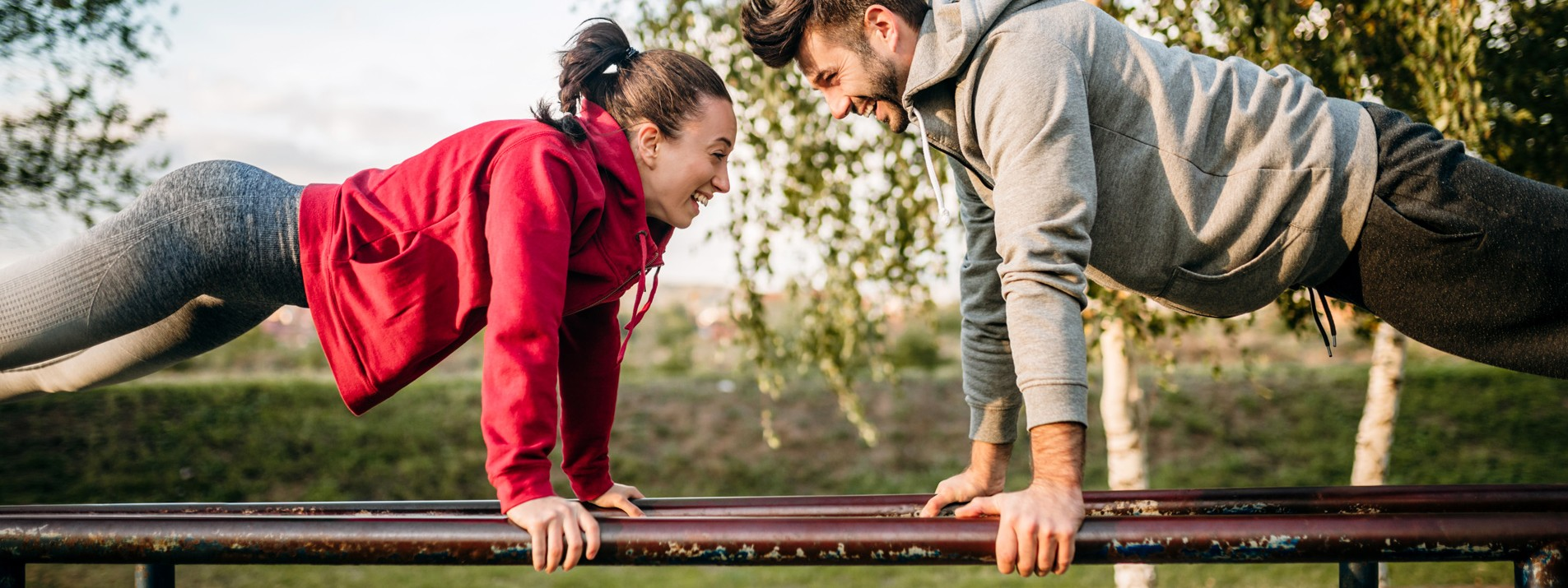 Eine etwa 30-jährige Frau und ein etwa 30-jähriger Mann machen Liegestütze auf einem Gerüst im Park.