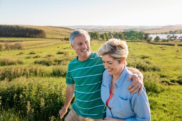 Ein etwa 60-jähriges Paar geht im Sonnenlicht über eine Wiese spazieren.