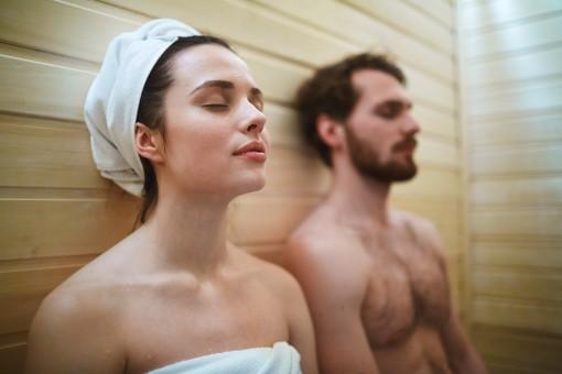 Mann und Frau mit geschlossenen Augen in der Sauna.