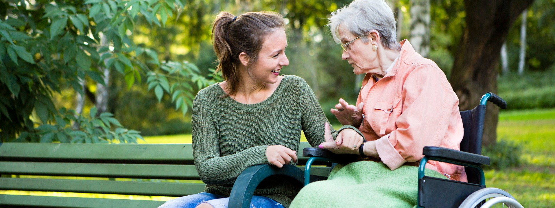 Junge Frau unterhält sich mit Seniorin, welche im Rollstuhl sitzt