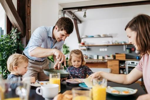 Vater serviert Spiegelei zum Frühstück mit Frau und zwei kleinen Kindern
