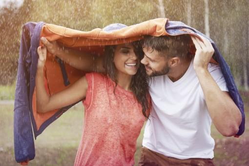 Ein Paar läuft durch strömenden Regen. Als Regenschutz haben sie eine Jacke über ihre Köpfe geworfen. Beide schauen sich lächelnd an.
