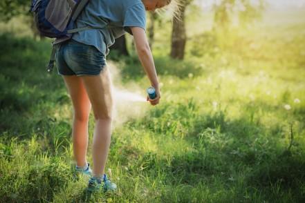 Mädchen spüht Insektenschutz auf Bein