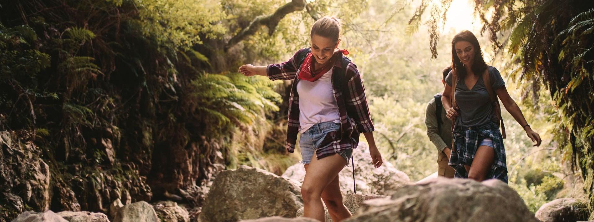 Drei etwa 25 jährige Personen wandern durch ein ausgetrocknetes steiniges Flussbett in der Natur.