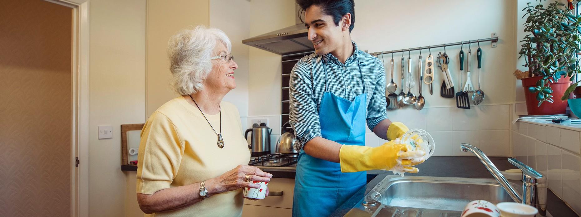 Mann hilft Seniorin beim Spülen