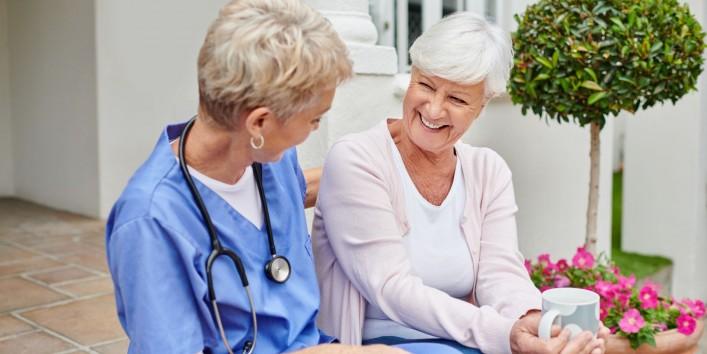 Eine Seniorin sitzt mit einer Ärztin auf einer Treppe. Die Seniorin hält eine Tasse in der Hand. Beide lächeln sich an.