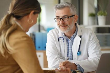 Eine Frau mittleren Alters sitzt in einer Arztpraxis und lässt sich von einem Arzt in weißem Kittel beraten.
