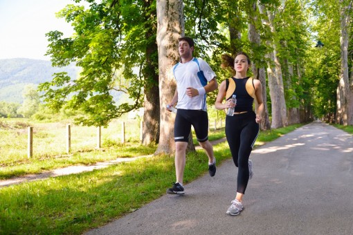 Ein junges Paar joggt gemeinsam einen asphaltierten Weg in der Natur entlang. Beide schauen konzentriert und tragen jeweils eine Wasserflasche mit sich.