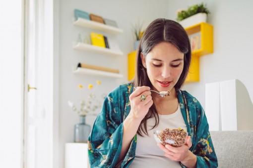 Eine etwa 30-jährige Frau sitzt auf dem Sofa und isst Müsli.