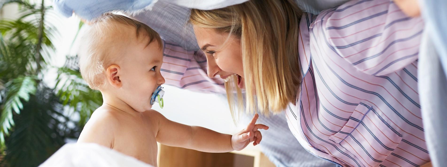 Mutter mit Baby spielend im Bett