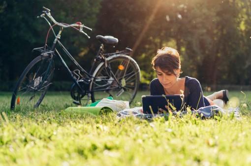 Eine etwa 30-jährige Frau liegt im Sommer entspannt mit einem Tablett auf der Wiese.
