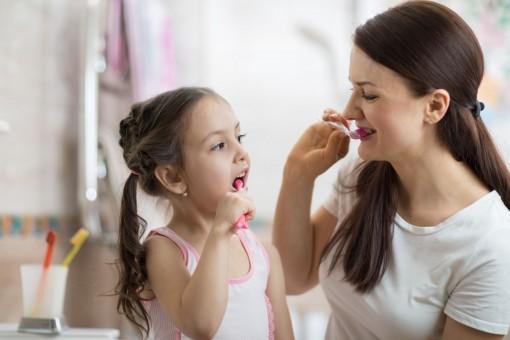 Eine etwa sechs jähriges Mädchen putzt mit Ihrer Mutter gemeinsam die Zähne. Beide schauen sich währenddessen an.