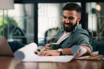 Ein etwa 30 jähriger Mann sitzt an einem Schreibtisch und hält eine Tasse in der rechten Hand. Vor ihm liegen Unterlagen und sein Laptop. Er lächelt.