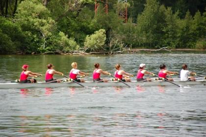 Acht Frauen rudern mit einem Kanu auf einem Fluss entlang.