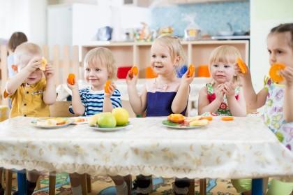 Kinder an einem Esstisch in einer Kita beim Essen.