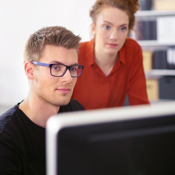 Ein circa 18-jähriger Auszubildender und eine circa 19-jährige Auszubildende schauen gemeinsam auf einen Bildschirm.