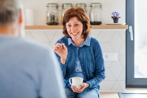 Ein 70-jähriger Mann und eine 70-jährige Frau unterhalten sich in der Küche.
