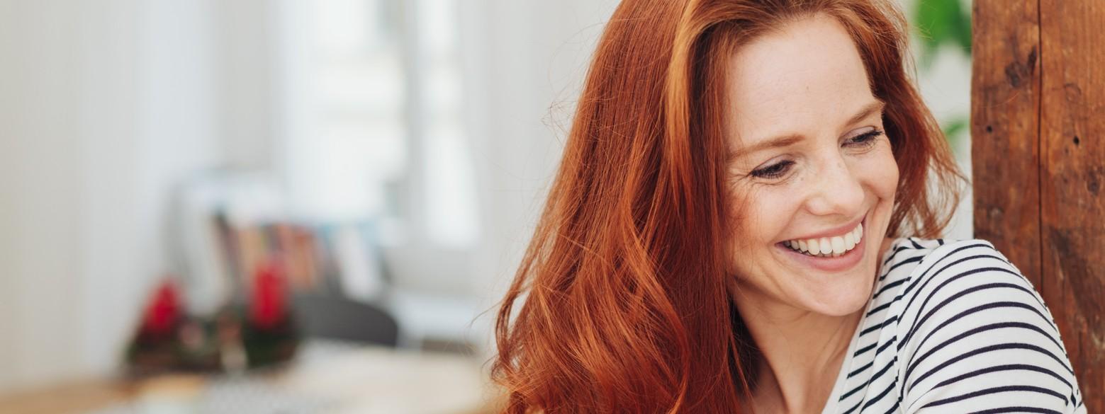 Eine rothaarige junge Frau hat einen gestreiften Pullover an, sitzt in einer Wohnung und lächelt.