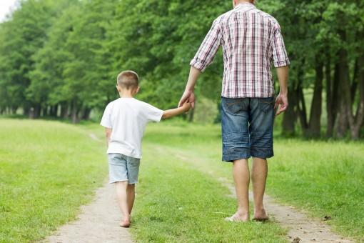 Ein Vater läuft mit seinem Sohn einen Feldweg an einer Wiese entlang. Beide fassen sich an den Händen. Sie laufen barfuß.