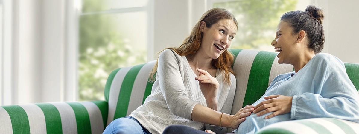 Zwei glücklich lächelnde Frauen sitzen vertraut auf dem Sofa und fühlen mit ihren Händen den Babybauch der Schwangeren.