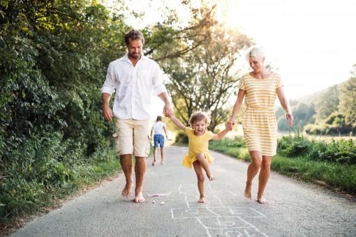 Eine kleine Familie läuft barfuß einen asphaltierten Weg entlang.