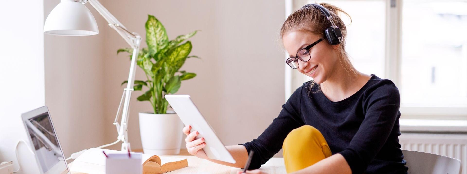 Ein etwa 15 jähriges Mädchen sitzt an einem Schreibtisch. In der rechten Hand hält sie ein Tablet, mit der linken Hand macht sie Notizen.Vor ihr steht ein Laptop. Sie trägt Kopfhörer und lächelt.