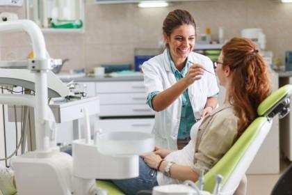 Eine junge Frau sitzt auf einem Zahnarzt stuhl und wird von einer Zahnärztin an den Zähnen behandelt. Beide befinden sich in einem Behandlungszimmer einer Zahnarztpraxis.