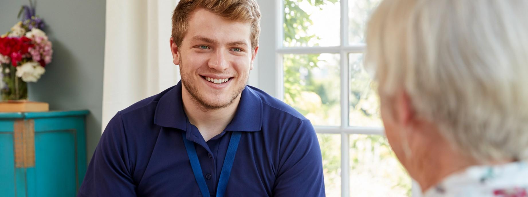 Ein junger Mann mit blauen T-Shirt sitzt auf dem Sofa und hat ein Klemmbrett in der Hand. Er lächelt eine blonde Frau an, die ihm gegenüber sitzt.