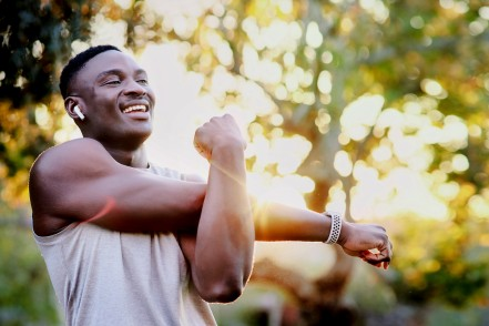 Ein sportlicher etwa 35-jähriger Mann dehnt seine Arme im Park und hört dabei Musik.