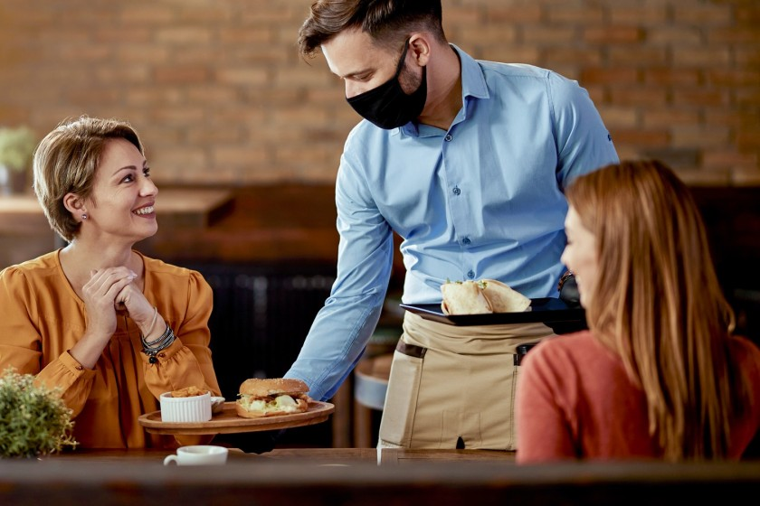 Zwei Frauen und ein Kellner mit Maske im Café