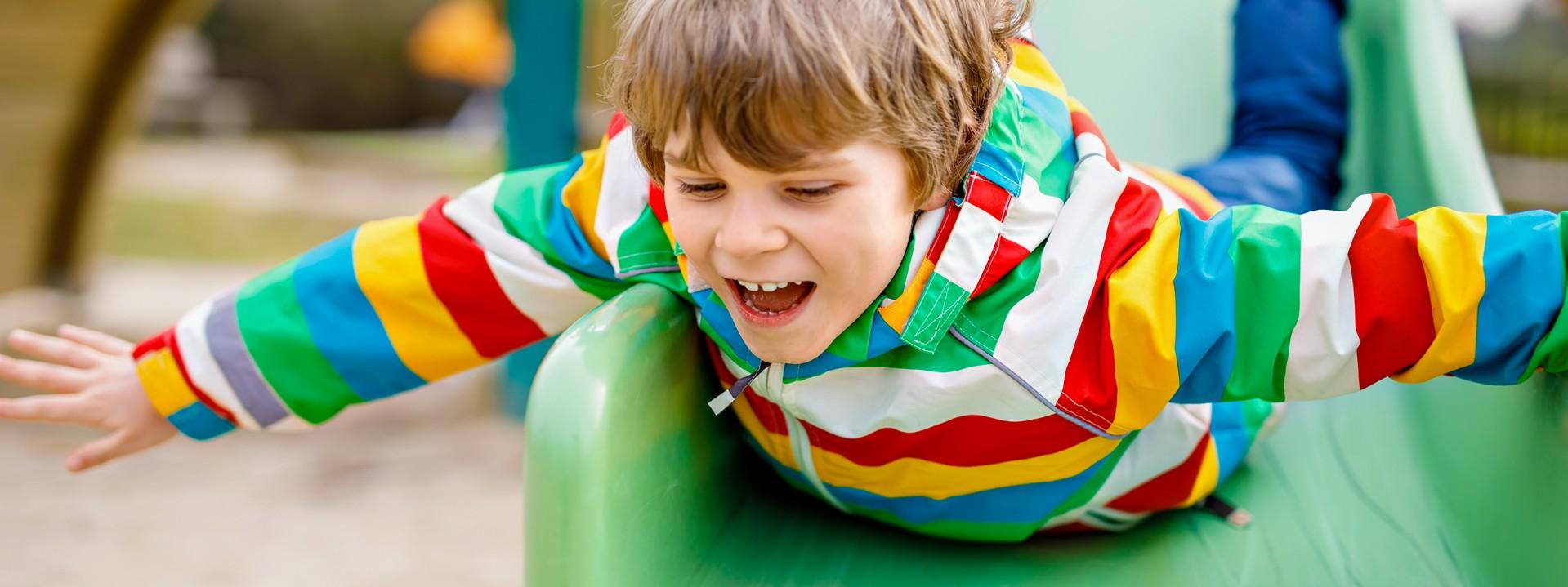 Kind rutscht Rutsche auf dem Bauch runter