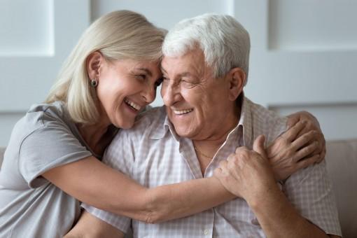 Ein älteres Pärchen umarmt sich innig. Beide lachen sich an,