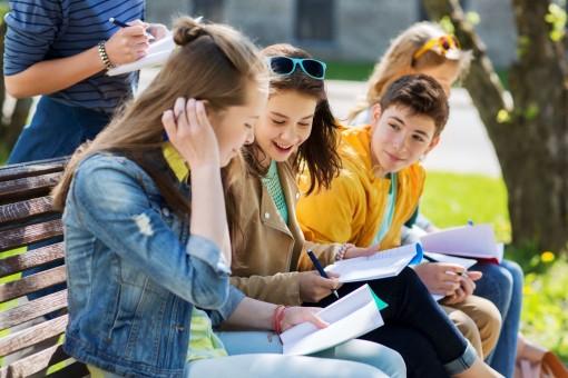 Zwei Schülerinnen und ein Schüler sitzen gemeinsam auf einer Bank im Parl. Sie lösen gemeinsam Schulaufgaben in einem Heft.
