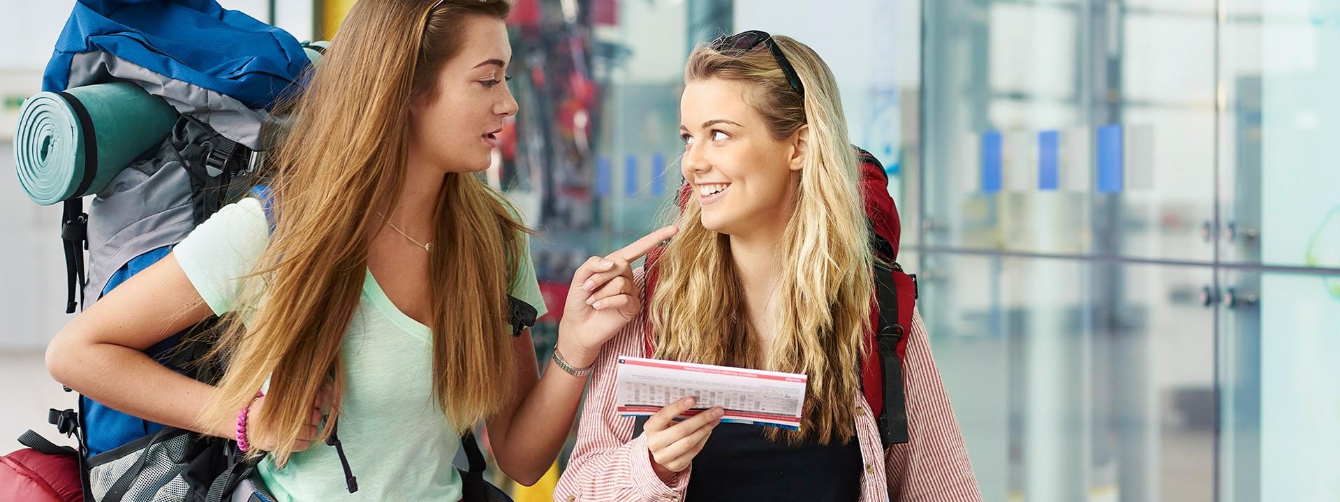 Zwei junge Frauen mit viel großem Reisegepäck unterhalten sich freundlich lächeln.