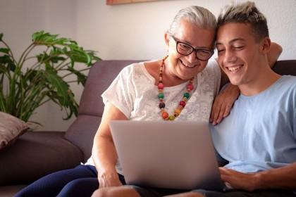 Eine Seniorin sitzt mit ihrem etwa 15 jährigen Enkel auf der Couch im Wohnzimmer. Beide schauen lächelnd auf einen Laptop.