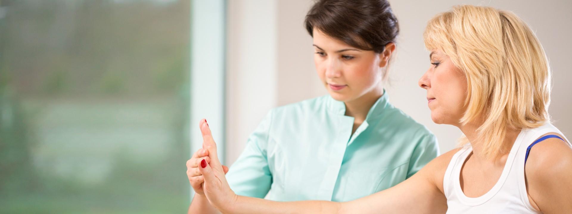 Eine blonde Frau wird von einer brünetten Frau am rechten Arm behandelt.