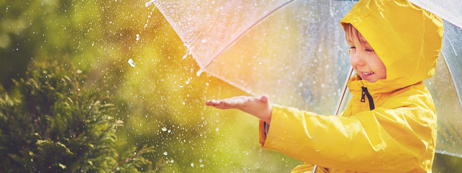 Ein Junge mit gelben Regenmantel und Reegenschirm genießt den Reegen