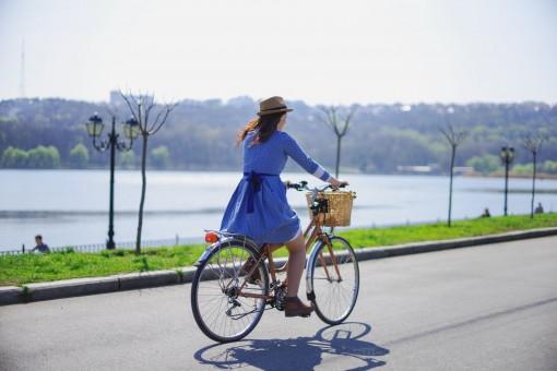 Eine junge Frau fährt mit Ihrem Fahrrad an eine Uferpromenade entlang.