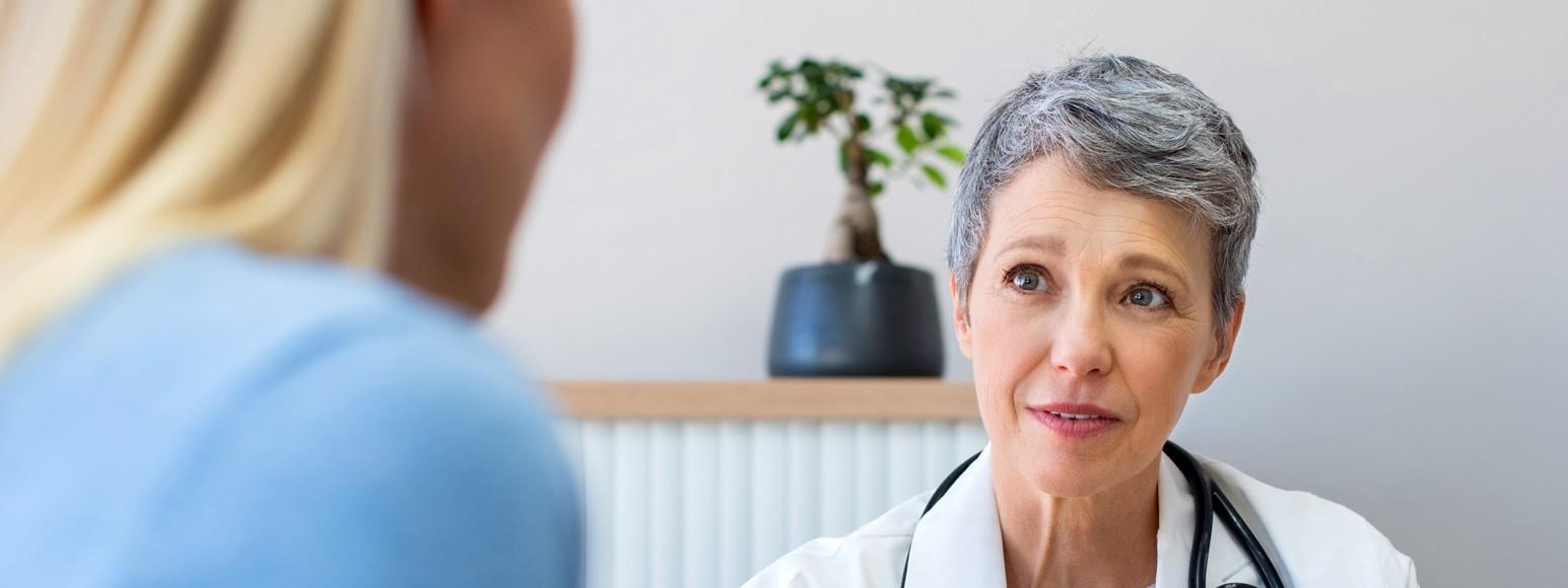 Eine Ärztin sitzt eine Patientin gegenüber und berät sie.