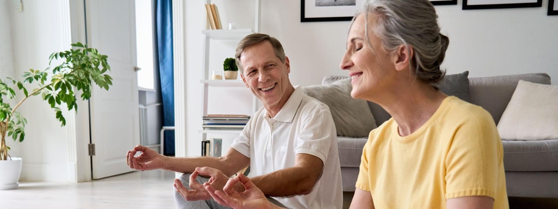 Ein etwa 60-jähriges Paar sitzt im Wohnzimmer auf zwei Sportmatten und macht lächelnd Yoga-Übungen.