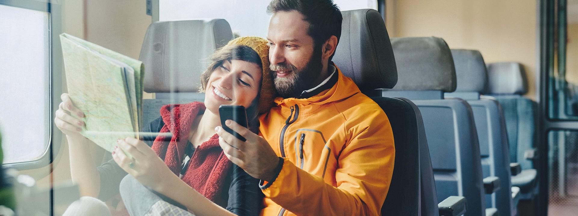 Reisendes Paar sitzt lächelnd im Zug und studiert die Route per Karte und Smartphone.