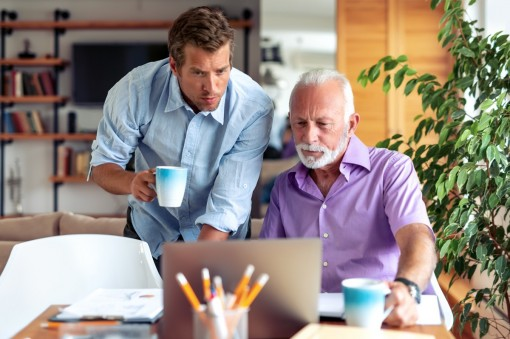 Ein 40-jähriger Mann und sein 70-jähriger Vater schauen zusammen auf einen Laptop.