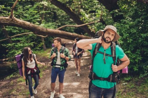 Vier etwa 30 jährige Personen laufen durch einen Wald. Der Mann im Vordergrund fest sich genervt an den Hals. Er wird von Mücken geplagt.