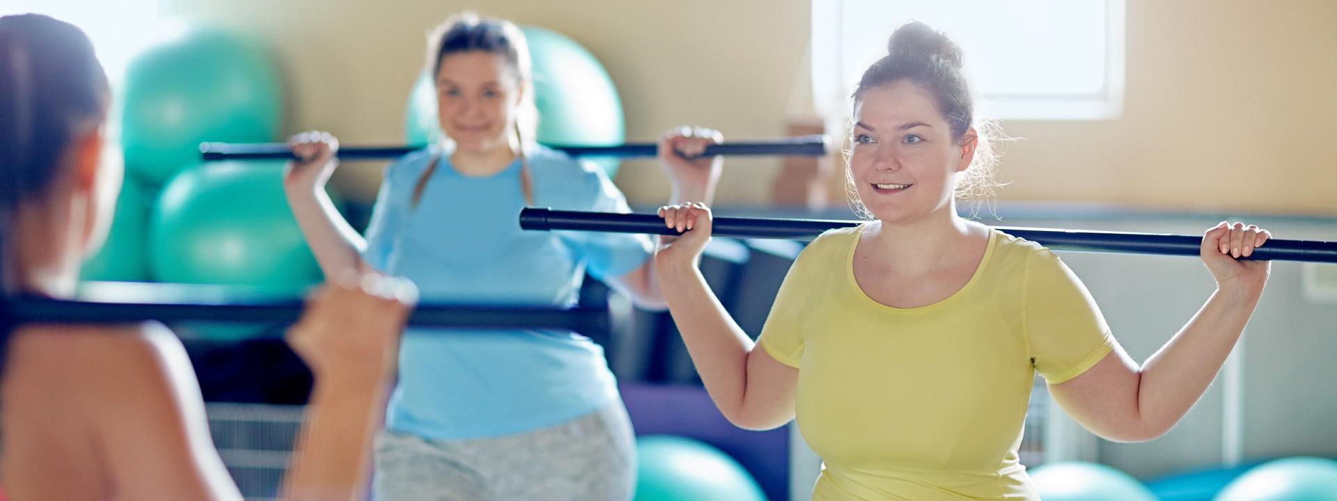 Drei Frauen machen zusammen Sport und mit grünen Gymnastikbällen im Hintergrund.