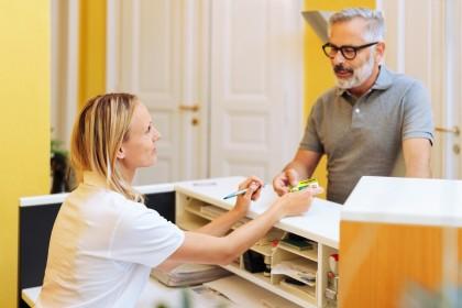 Ein etwa 55 jähriger Mann steht am Empfangstresen einer Arztpraxis. Er streckt der Arzthelferin seine Versichertenkarte entgegen.