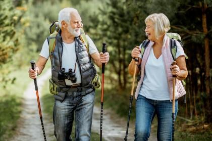 Älteres Paar beim Wandern mit Stöcken im Wald.